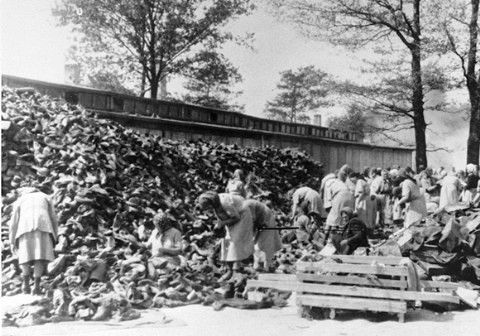 Auschwitz women inmates sort through a huge pile of shoes from the transport of Hungarian Jews